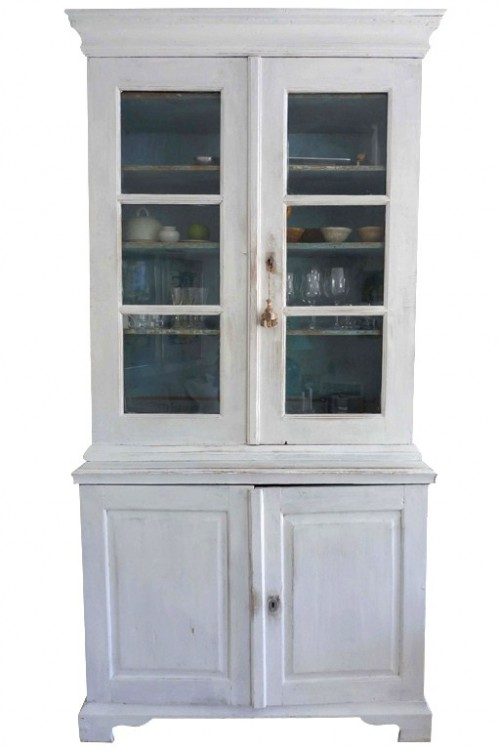 A white painted cabinet from Sweden with glass doors and a cabinet base.