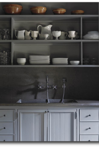 Gray Painted Cabinets With White Dinnerware Displayed